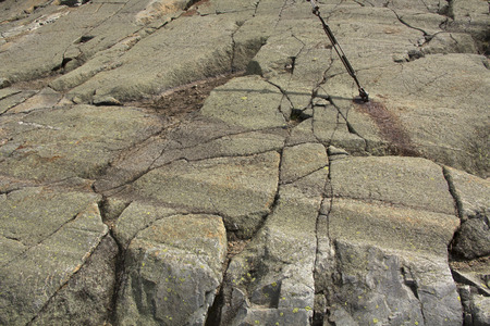 grooves: Glacial grooves in bedrock near summit of Mt. Kearsarge, New Hampshire, with embedded steel cable anchor for the fire tower, horizontal image.