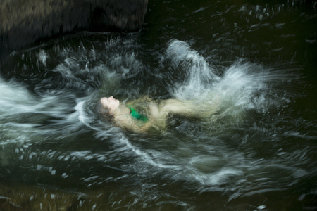 against the current: Young woman swimming with a vigorous backstroke against the current of the Sugar River, Newport, New Hampshire.