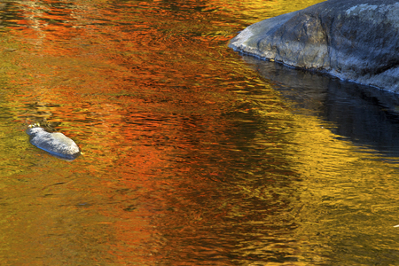 Brilliant palette of fall foliage reflections among boulders in the waters of the Farmington River in Canton, Connecticut. 스톡 콘텐츠