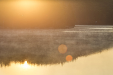Sunrise flare at Mountain View Lake in Sunapee, New Hampshire, with trees and reflections.