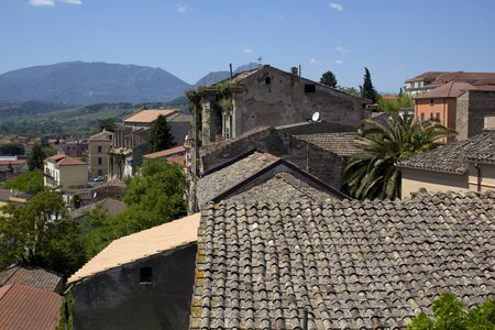 City of Benevento,Campania, Italy, with the Taburno Mountains in the background. There is a mixture of old and new with satellite dishes among the decaying plaster walls and tile roofs Stock Photo