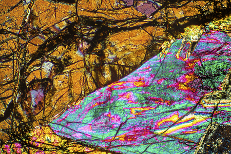 Wedges of brown, purple, and aqua shapes in abstract micrograph of peridotite rock, at 40x with polarization. Stock Photo