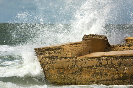 Waves of a heavy surf break with explosive force on concrete remains of Battery Bigelow at Fort De Soto Park in St. Petersburg, Florida.