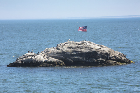American flag unfurled in the breeze on Wigwam Rock in Niantic Bay in East Lyme, Connecticut. Editorial