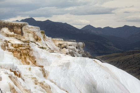 Geothermal flow of hot, carbonate rich water, forms cascading, dark orange travertine terraces, with mountains in the background, at Mammoth Hot Springs in Yellowstone National Park, Wyoming.