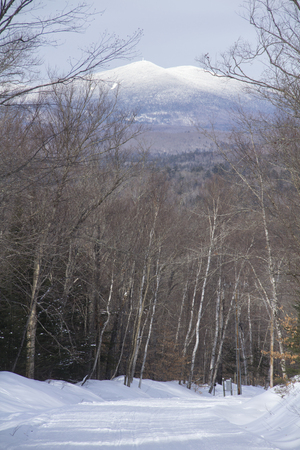 Snowmobile and hiking trail covered in snow in winter on Bald Mountain in Rangeley, Maine, with a view of Kennebago Mountain in the distance.