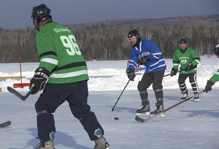 Men's teams compete on the ice at the 11th annual New England Pond Hockey Festival on Haley Pond in Rangeley, Maine.