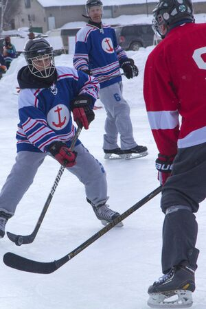 Men's teams compete on the ice at the 11th annual New England Pond Hockey Festival on Hayley Pond in Rangeley, Maine.