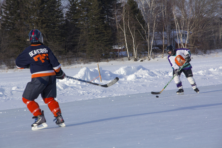 Womens teams compete on the ice at the 11th annual New England Pond Hockey Festival on Haley Pond in Rangeley, Maine.