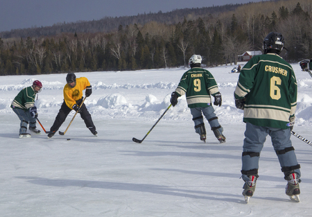 Mens teams compete on the ice in the 11th annual New England Pond Hockey Festival on Hayley Pond in Rangeley, Maine. Editorial