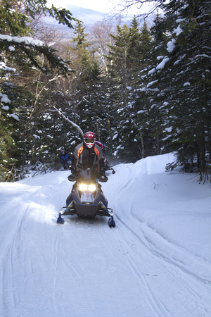 Snomobilers climbing a groomed trail near Bald Mountain in Rangeley, Maine in early February. Редакционное