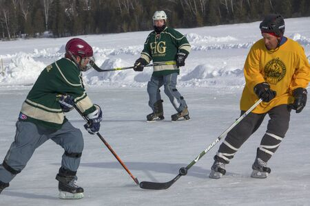 Men's teams compete on the ice in the 11th annual New England Pond Hockey Festival on Hayley Pond in Rangeley, Maine.