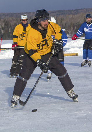 Mens teams compete on the ice at the 11th annual New England Pond Hockey Festival on Haley Pond in Rangeley, Maine. Editorial