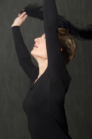 Belle jeune femme danseuse aux cheveux courts, vêtue d'une robe noire à col rond, jetant un boa noir duveteux sur sa tête en studio. Banque d'images - 91956723