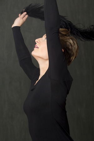 Attractive young woman dancer with short hair, in a scoop neck black dress, throwing a fuzzy black boa over her head in the studio.