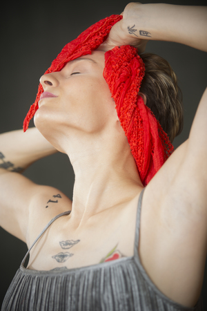 Attractive young woman dancer with short hair, head and shoulders only, holding a red scarf behind her neck and throwing her head back in the studio. Stock Photo