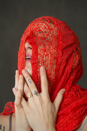 Attractive young woman dancer with short hair, head and shoulders only, holding a red scarf over her face in the studio. Stock Photo