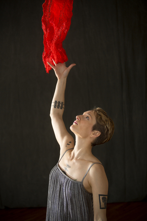 Attractive young woman dancer with short hair, in a silver bag dress with a red scarf floating above her in the studio.