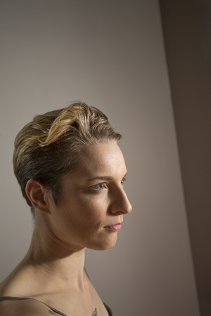 Attractive young woman dancer with short hair, head and shoulders profile in the studio.