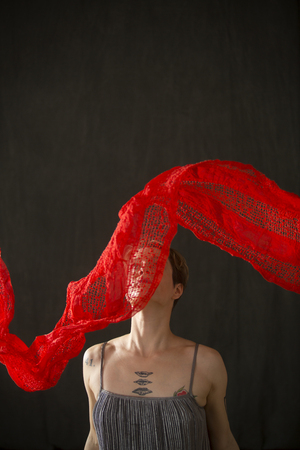 Attractive young woman dancer with short hair, in a silver bag dress with a red scarf floating over her face in the studio.