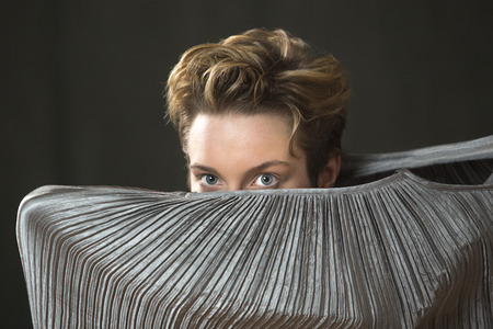 Contemporary young woman dancer with short hair, immersed in a silver bag dress, peering out with only her head emerging from the top, in the studio.
