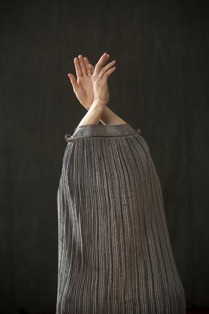 現代の若い女性ダンサーは、スタジオで、彼女の手だけが上から出てくる銀のバッグドレスに浸りました。 写真素材