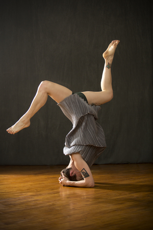 Young woman in silver bag dress holding a yoga headstand with legs apart and knees bent on the wood floor of the studio.