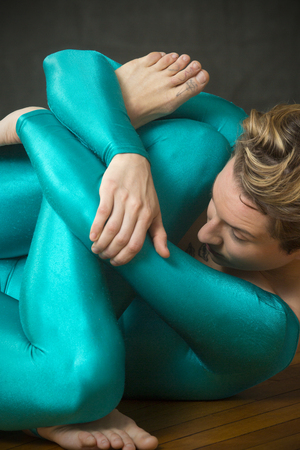 Contemporary young woman dancer with short hair, wearing a blue unitard body suit while lying on the wood floor of the studio with her arms and legs folded together. Stock Photo