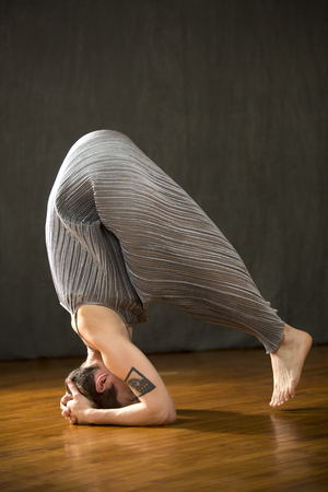 Young woman in silver bag dress beginning a yoga headstand with feet barely off the wood floor of the studio. Stock Photo