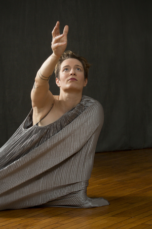 Contemporary young woman dancer with short hair in a silver bag dress, reaching out with one arm extended.