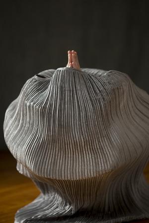 O dançarino contemporâneo da jovem mulher imergiu em um vestido de prata do saco, com somente suas mãos que emergem do alto, no estúdio. Foto de archivo - 92164302