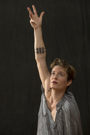Contemporary young woman dancer with short hair in a silver bag dress, reaching up with one arm extended.