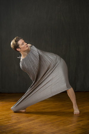 Contemporary young woman dancer with short hair, lunging sideways while mostly immersed in a silver bag dress, with only her head and a leg showing, in the studio.