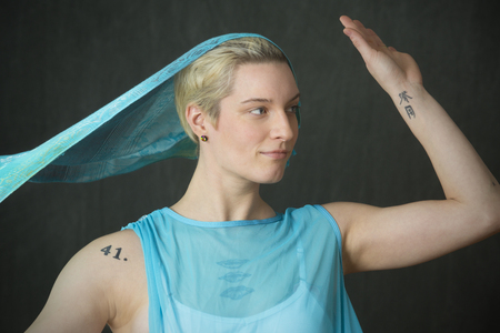 Head and shoulders portrait of young woman dancer with short blonde hair with a blue scarf flowing off the top of her head.