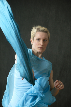 Active young woman dancer with short blonde hair, in a white leotard with a blue cape, throwing a blue scarf in the studio.