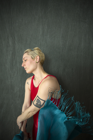 Exhausted young woman dancer with short blonde hair, in a red unitard holding a blue scarf while lost in thought in the studio. Banque d'images
