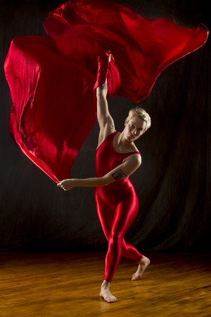 Active young woman dancer with short blonde hair, in a red unitard, dramatically swirling red fabric in the studio.