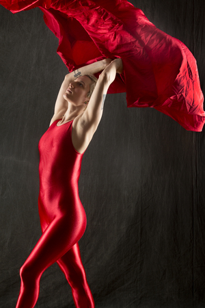 Active young woman dancer with short blonde hair, in a red unitard, swirling red fabric over her head in the studio. Stock Photo