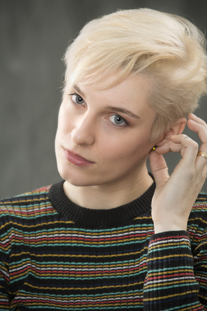 Serious head and shoulders portrait of young blonde woman in colorful striped shirt looking directly into camera.