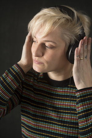 Head and shoulders of young woman with short blonde hair in a striped shirt, wearing headphones and groovin to the music.
