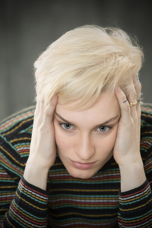 Serious head and shoulders portrait of young blonde woman in colorful striped shirt with hands on her temples. Stock Photo