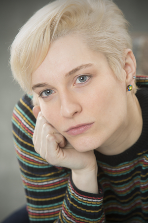 Serious head and shoulders portrait of young blonde woman in colorful striped shirt with head resting on hand. Stock Photo