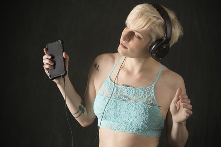 Young blonde woman in blue camisole with headphones on and holding a cell phone, looking away lost in music, half length.