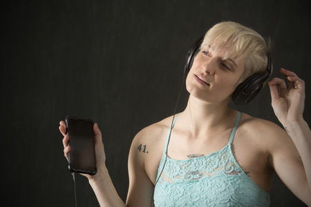 Half length portrait of young blonde woman in blue camisole with headphones on and holding a cell phone.