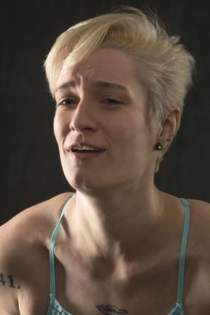 青いキャミソールを着て、大きな痛みを抱えているように見える若いブロンドの女性の同情的な頭と肩の肖像画。