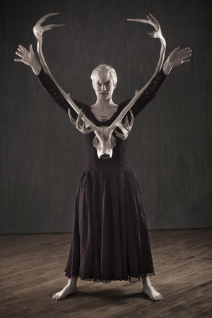 Desaturated view of young blonde woman standing in a vintage dress with caribou antlers between her raised arms.