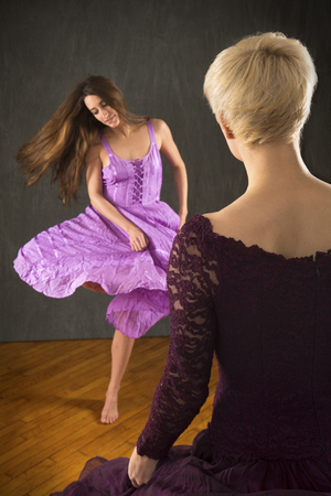 Two young women in purple dresses dancing with enthusiasm on a hardwood floor in the studio.