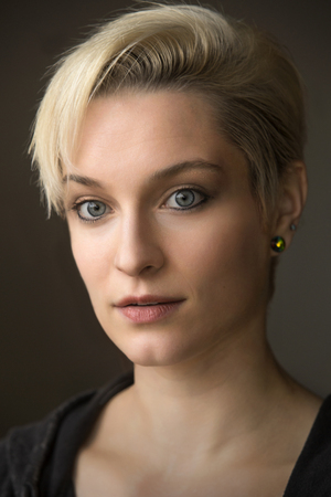 Head and shoulders portrait of  beautiful young woman looking into camera, with short blonde hair in window light.