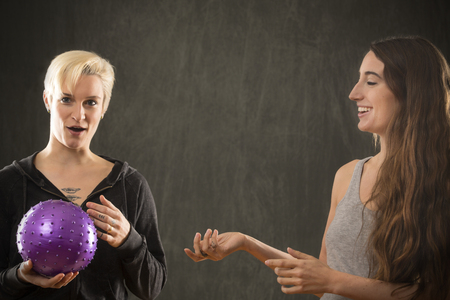 Two attractive young women friends in casual wear, playing with a purple ball in the studio against a gray background.