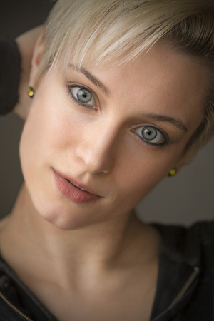 Head and shoulders portrait of  beautiful young woman with short blonde hair in window light.